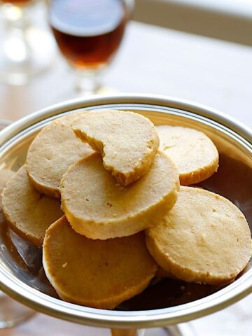 Cheddar CHeese Coins in a Silver Dish with a glass of port in the background