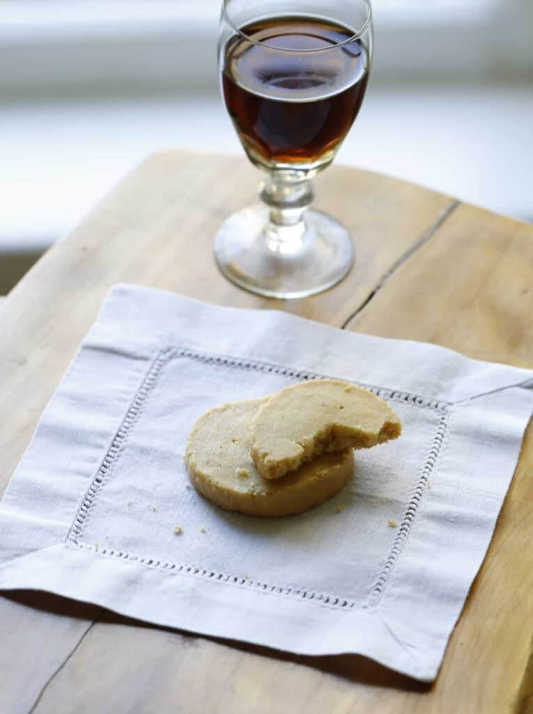 cheddar cheese coins on a linen napkin with a glass of port