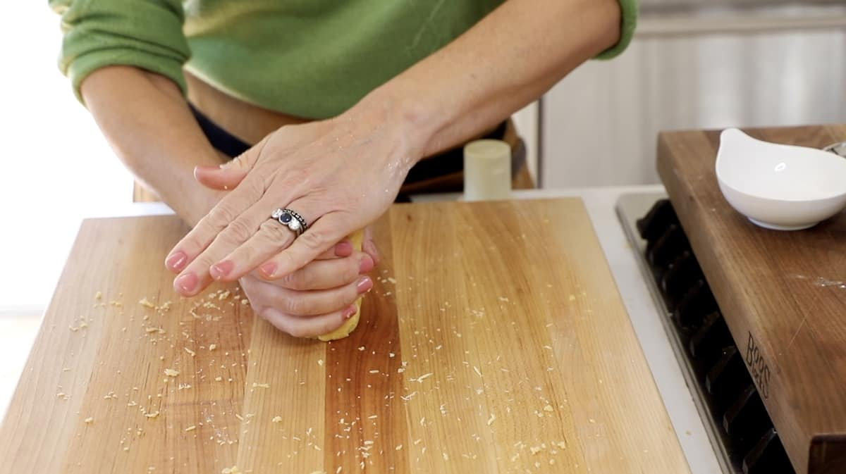 Stamping down the end of dough log on cutting board