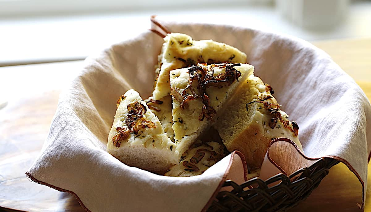A bread basket filled with slice focaccia bread topped with shallots