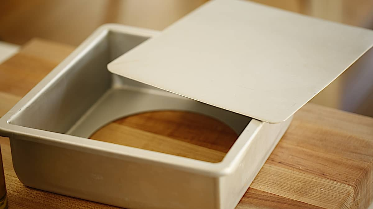a square cheesecake pan with a removable bottom on a cutting board