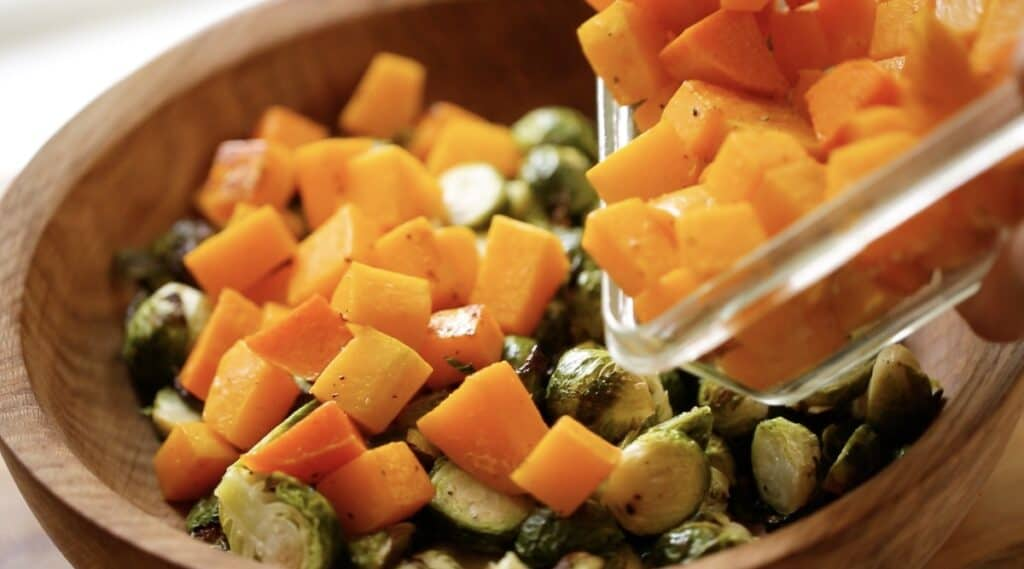 adding cooked butternut squash cubes to a salad bowl with Brussels sprouts