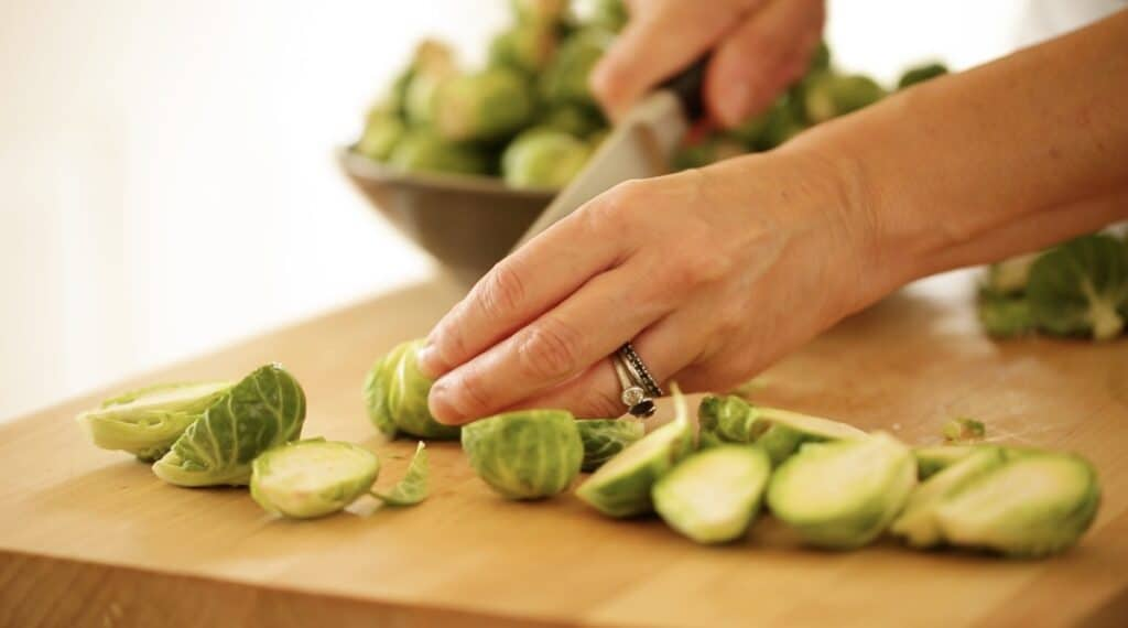 slicing brussle sprouts in half on a cutting board