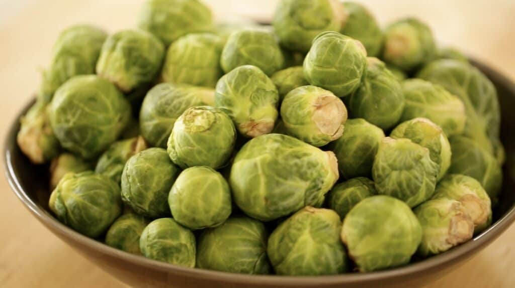a bowl of Brussels sprouts on a cutting board