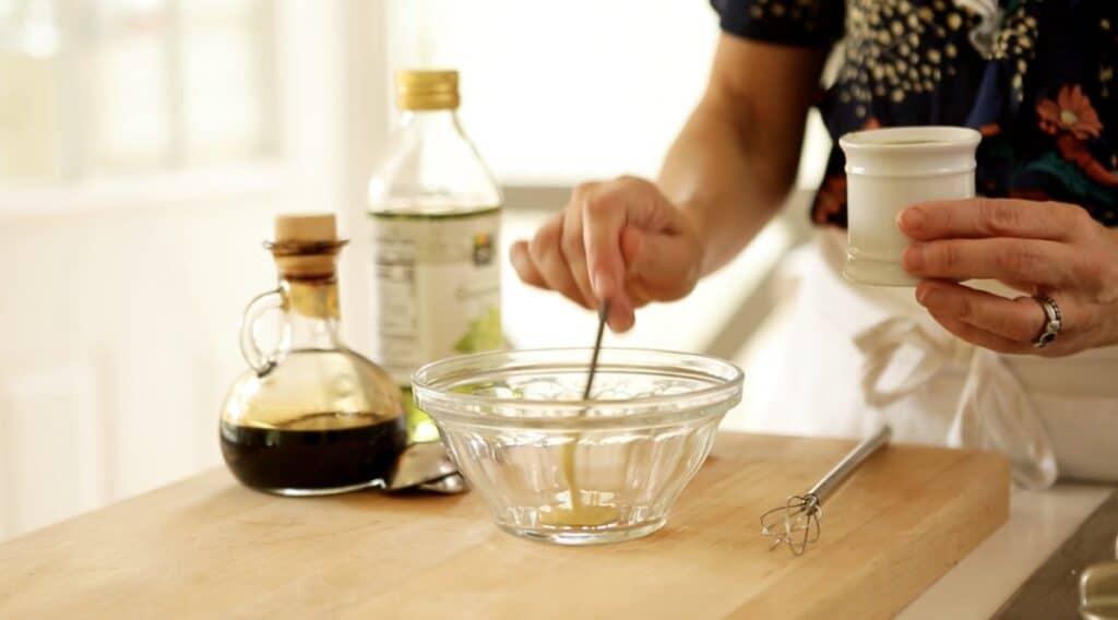 a person whisking together vinaigrette in a bowl