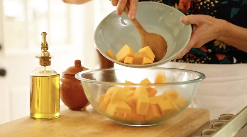 Adding cubed butternut squash to a clear bowl