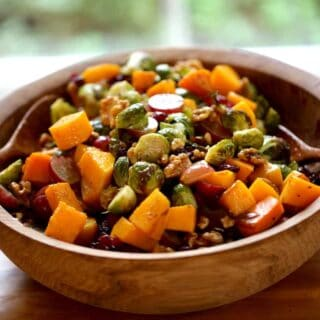 a harvest salad in a wooden bowl with wooden salad servers