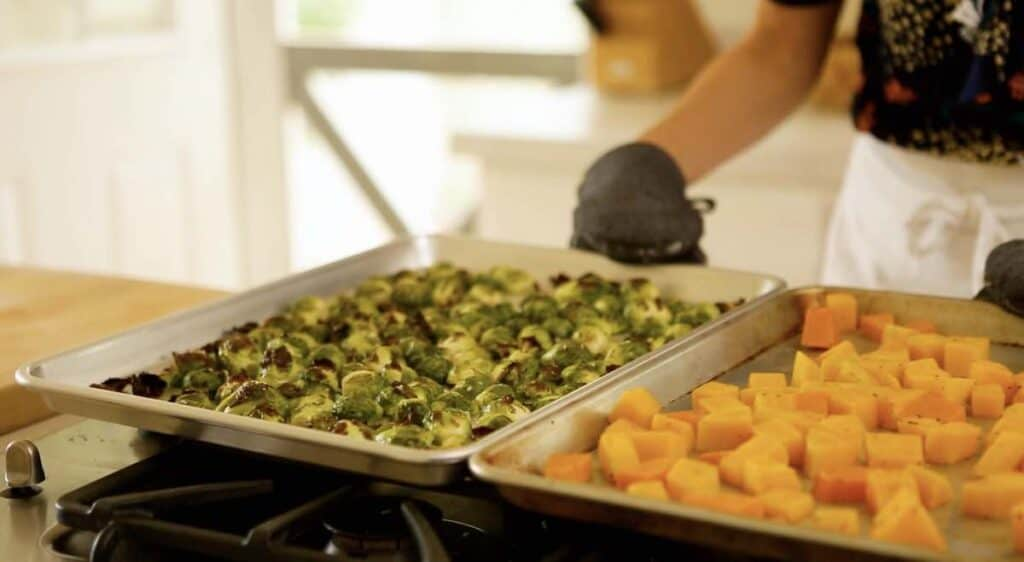 a person placing sheet pans filled with vegetables on a cooktop
