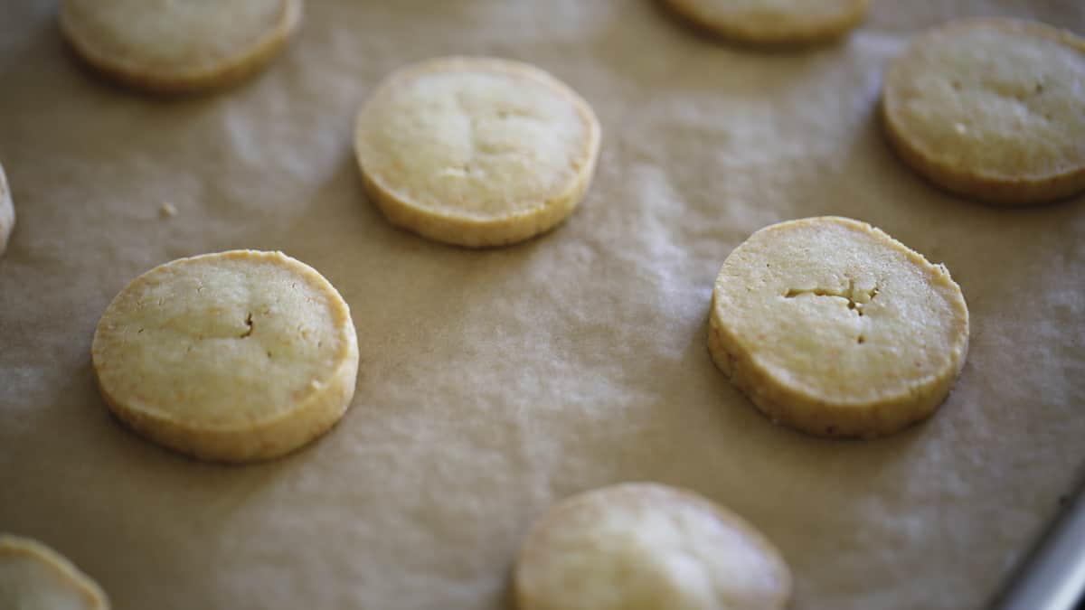 Cheese coins cooling on a parchment lined cookie sheet