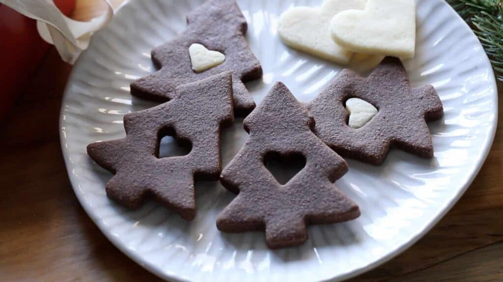 a plate of chocolate christmas tree cookies on a plate with sugar cookie hearts