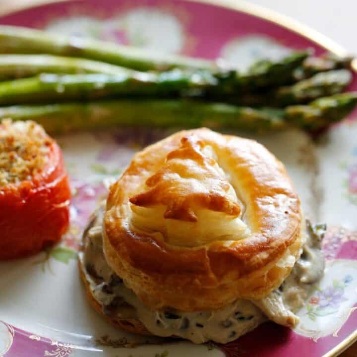 Bouchee a la reine in puff pastry on a plate with a roasted tomato and asparagus