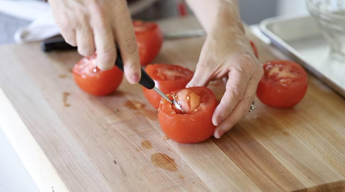 a person coring tomatoes with a melon baller