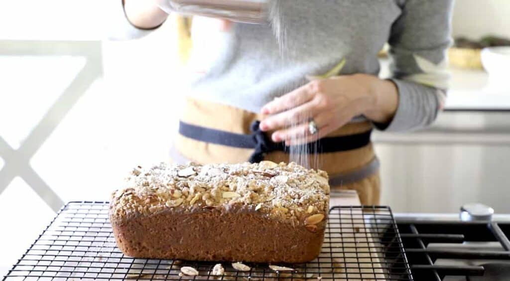 A person dusting a crumb cake loaf with powdered sugar