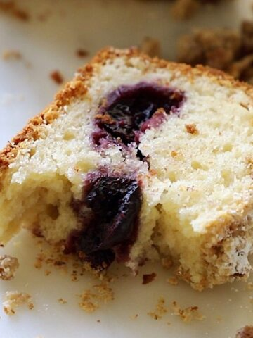 A slice of crumb cake with cherries baked inside