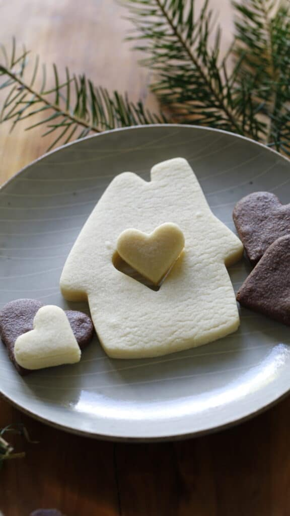 a vertical image of a House Christmas Cookie with a heart cut out