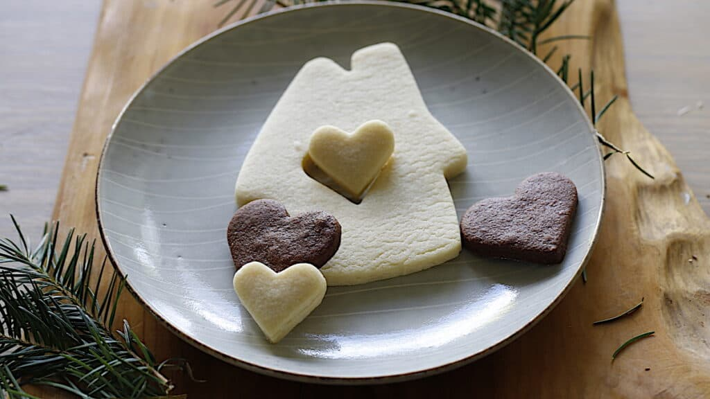 a sugar cookie in the shape of a house with a heart cut out in the center