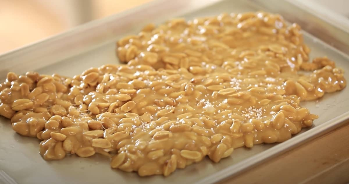 a mass of peanut brittle hardening on a sheet pan as it sets