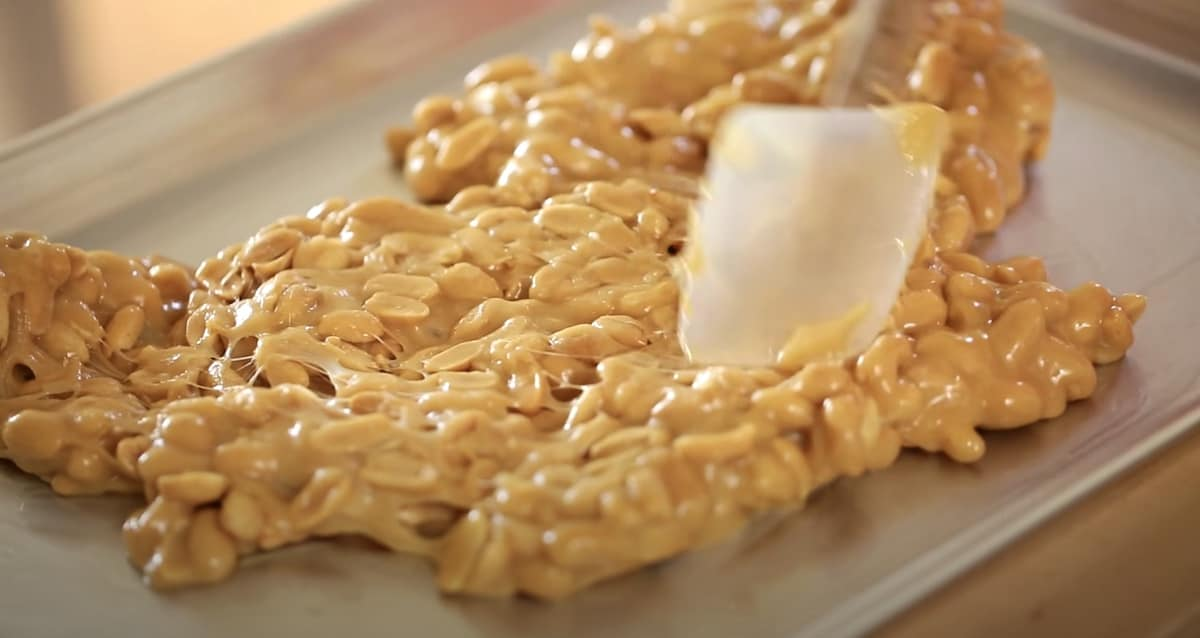 a spatula pressing down hot peanut brittle onto a sheet pan