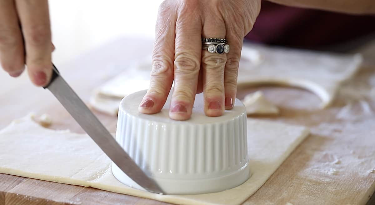 cutting a puff pastry round with a ramekin