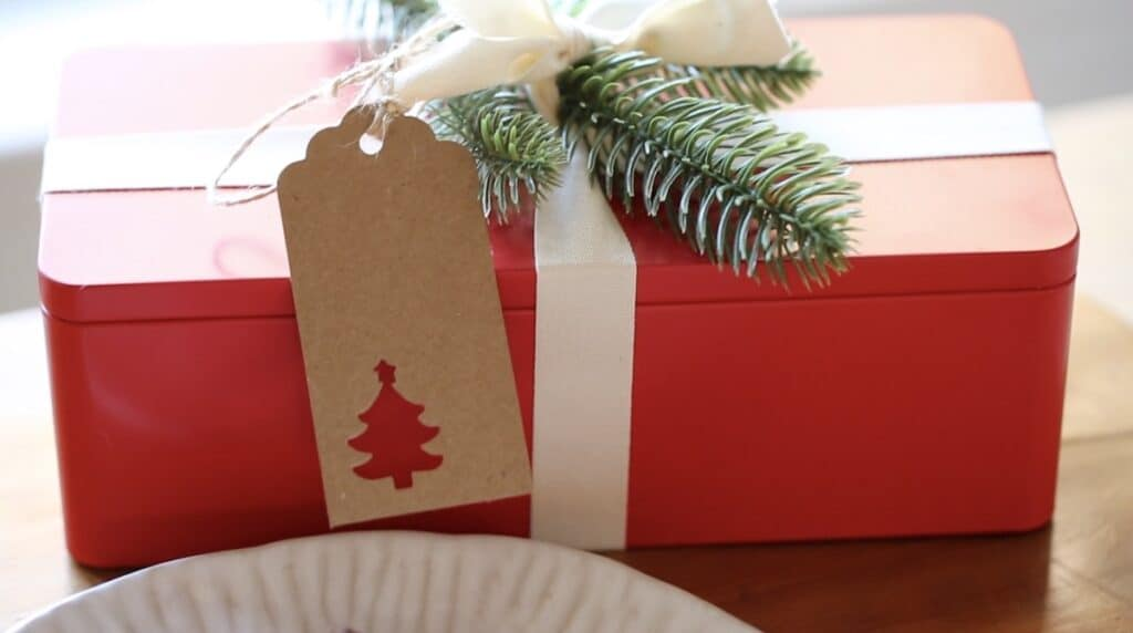 Red Cookie tin wraped in white ribbon and faux evergreen with Christmas Tree Gift Tag