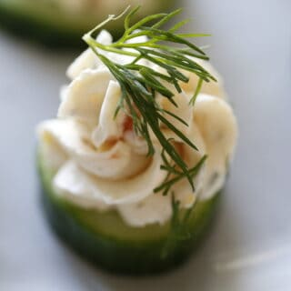 Close up of Salmon Mousse pipped on to a cucumber slice with fresh dill