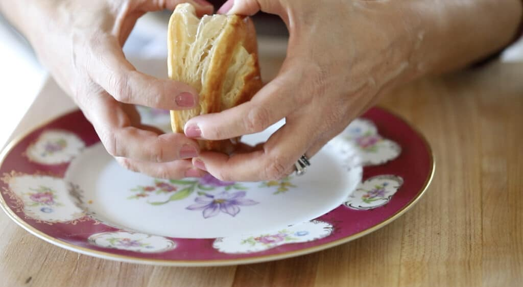 a Person Splitting a Puff Pastry Round with their hands over a holiday plate