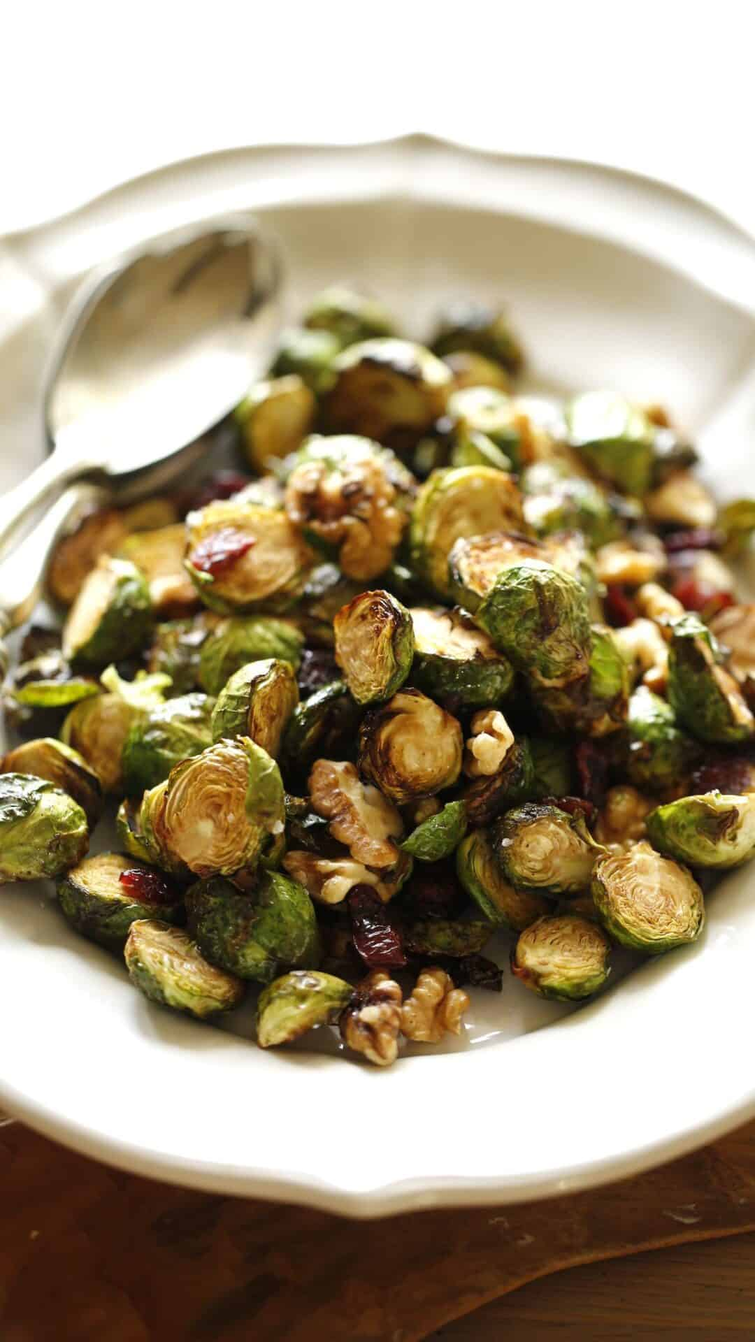 Brussel sprouts on a platter with a silver serving spoon
