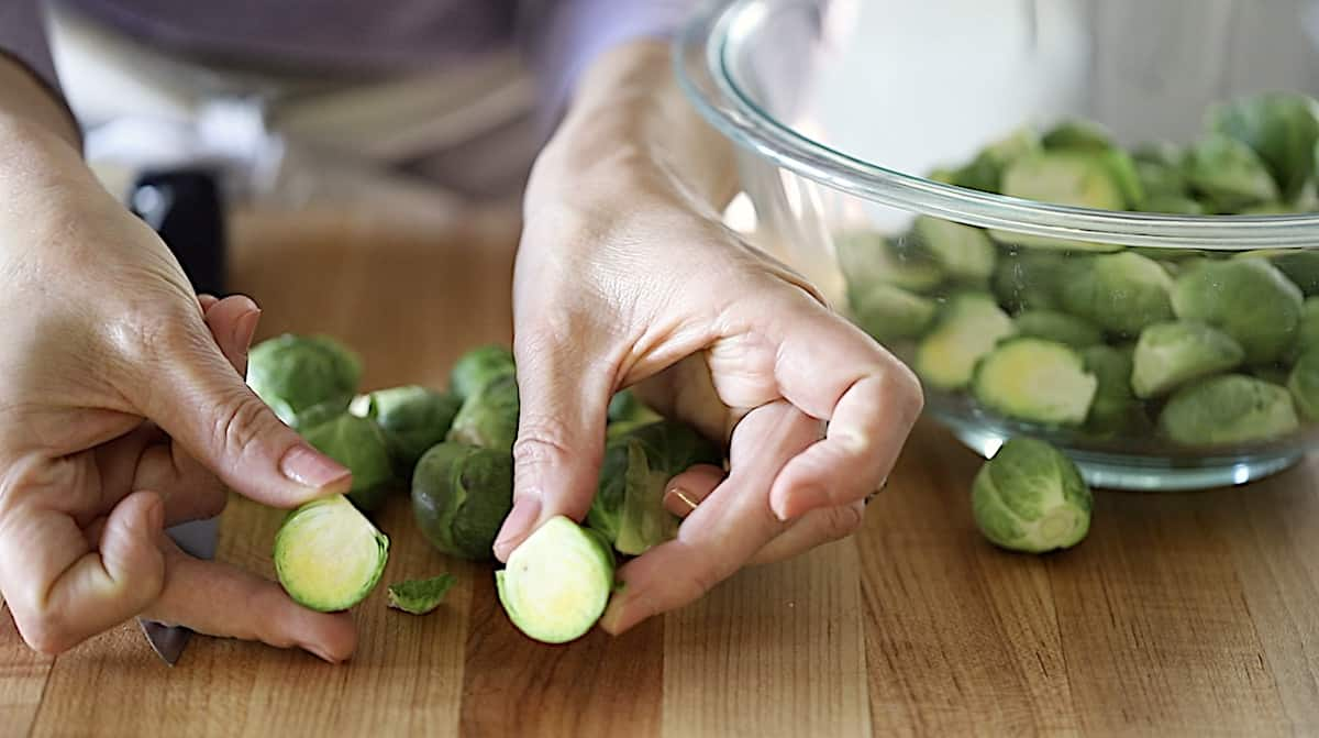 a person showing a brussel sprout cut in half