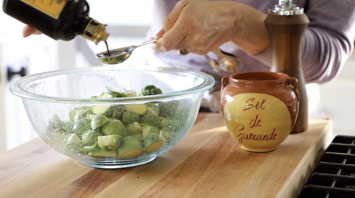 a person measuring a tablespoon of balsamic vinegar over a bowl of brussel sprouts