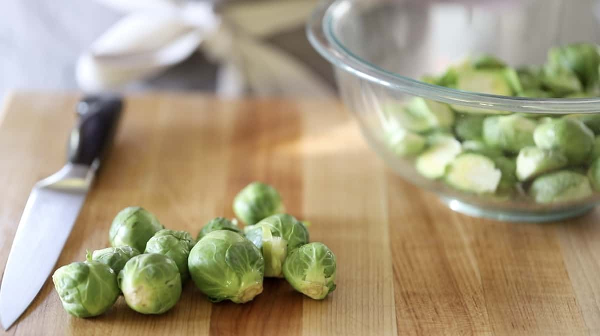 small brussel sprouts on a wooden cutting board with a glass bowl filled with sprouts in the background