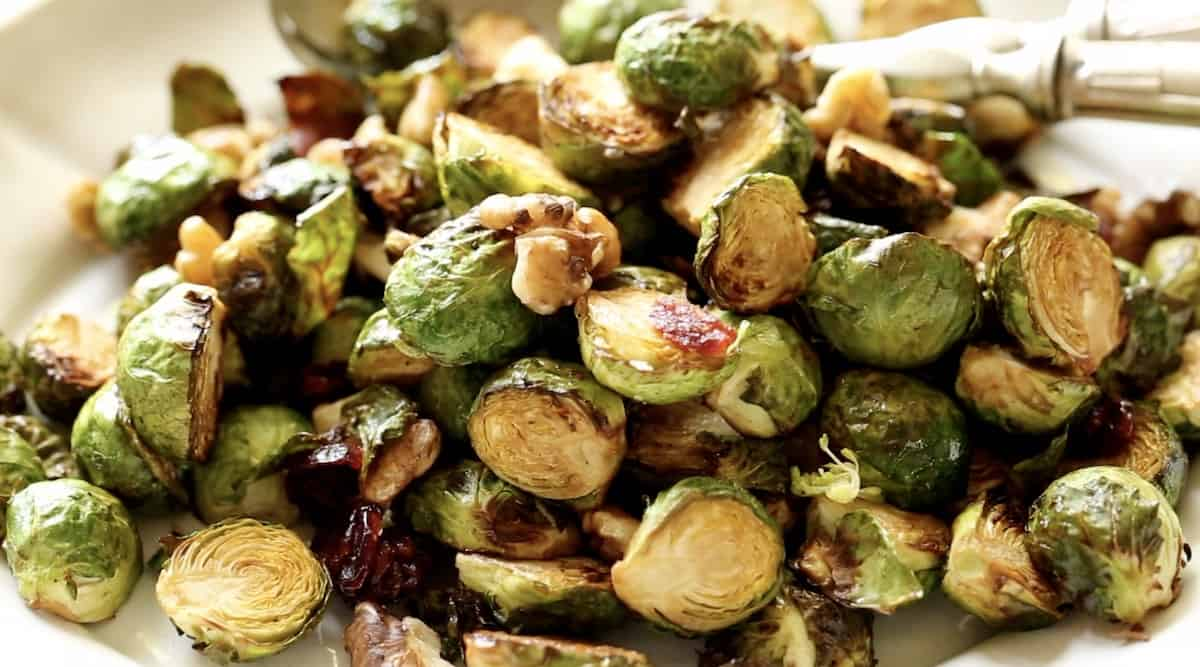 detail of brussel sprouts on a platter with buts and dried cranberries