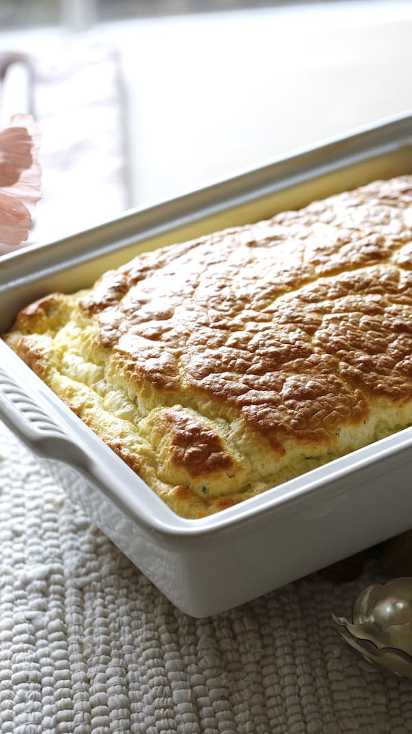 Vertical image of a breakfast souffle in a white casserole dish