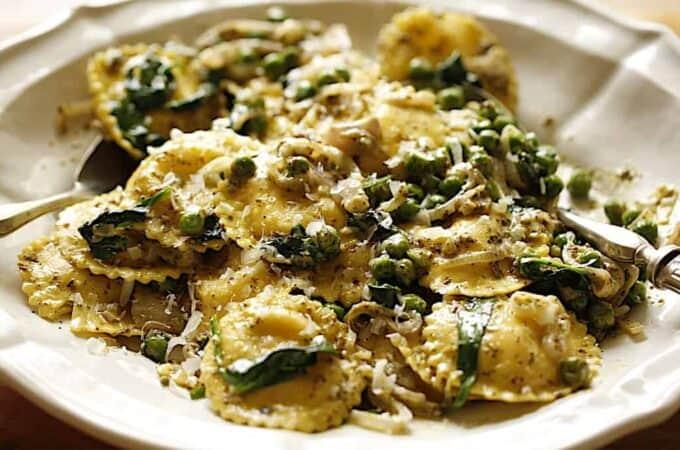 Ravioli with Pesto sauce and veggies on a white platter