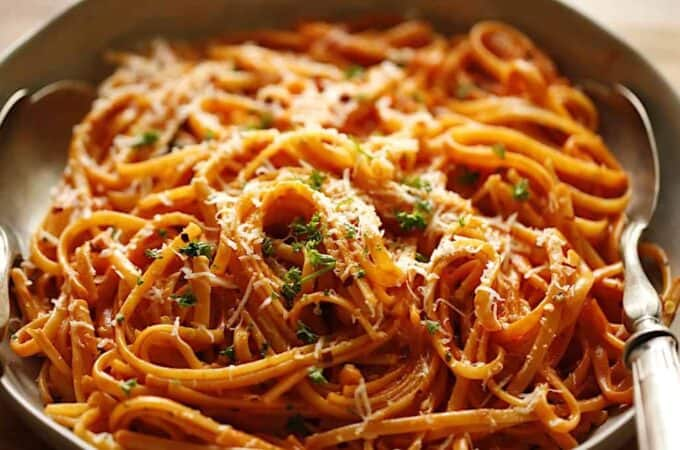 a close up of grated parmesan cheese and chopped parsley on linguine with a creamy tomato sauce