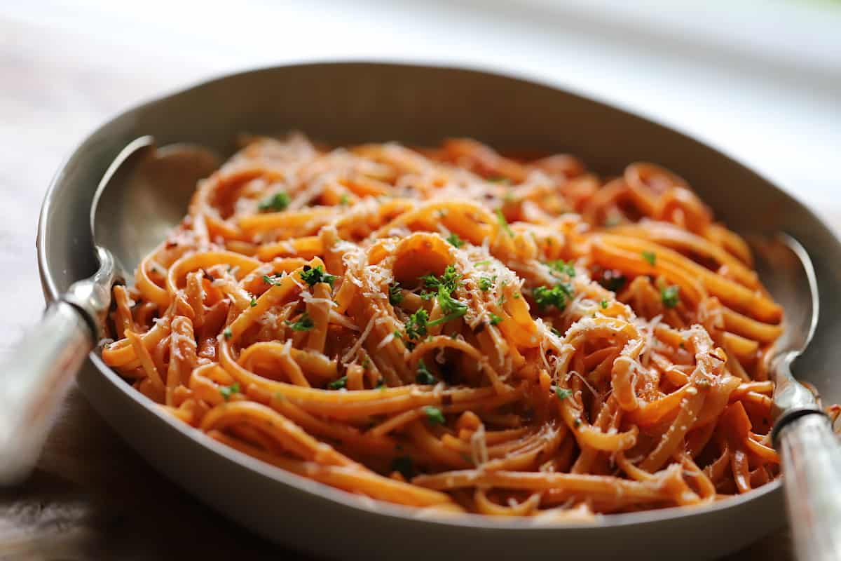 Creamy Tomato Saue Pasta in a gray serving bowl with silver serving poons