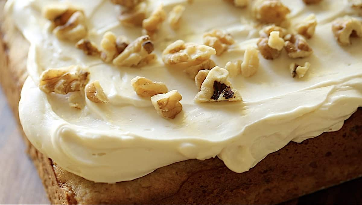 a detail of a cream cheese frosting whip on the corner of a cake.