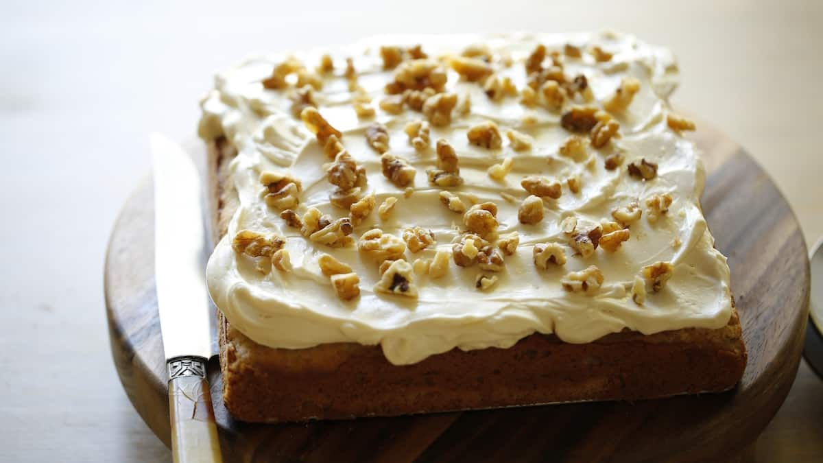 a whole banana cake with cream cheese frosting topped with walnuts on a board