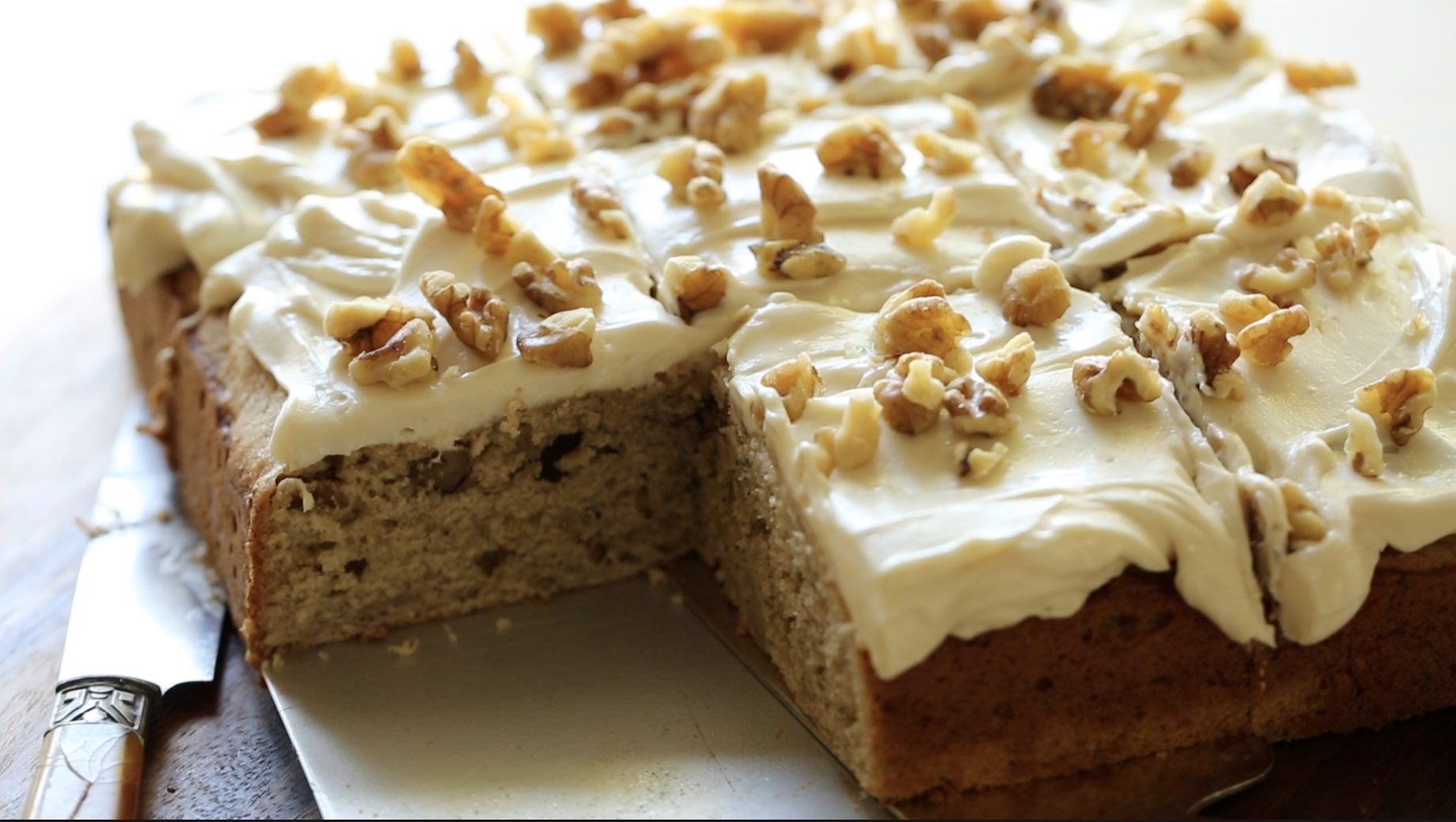 A whole banana cake with cream cheese frosting topped with nuts