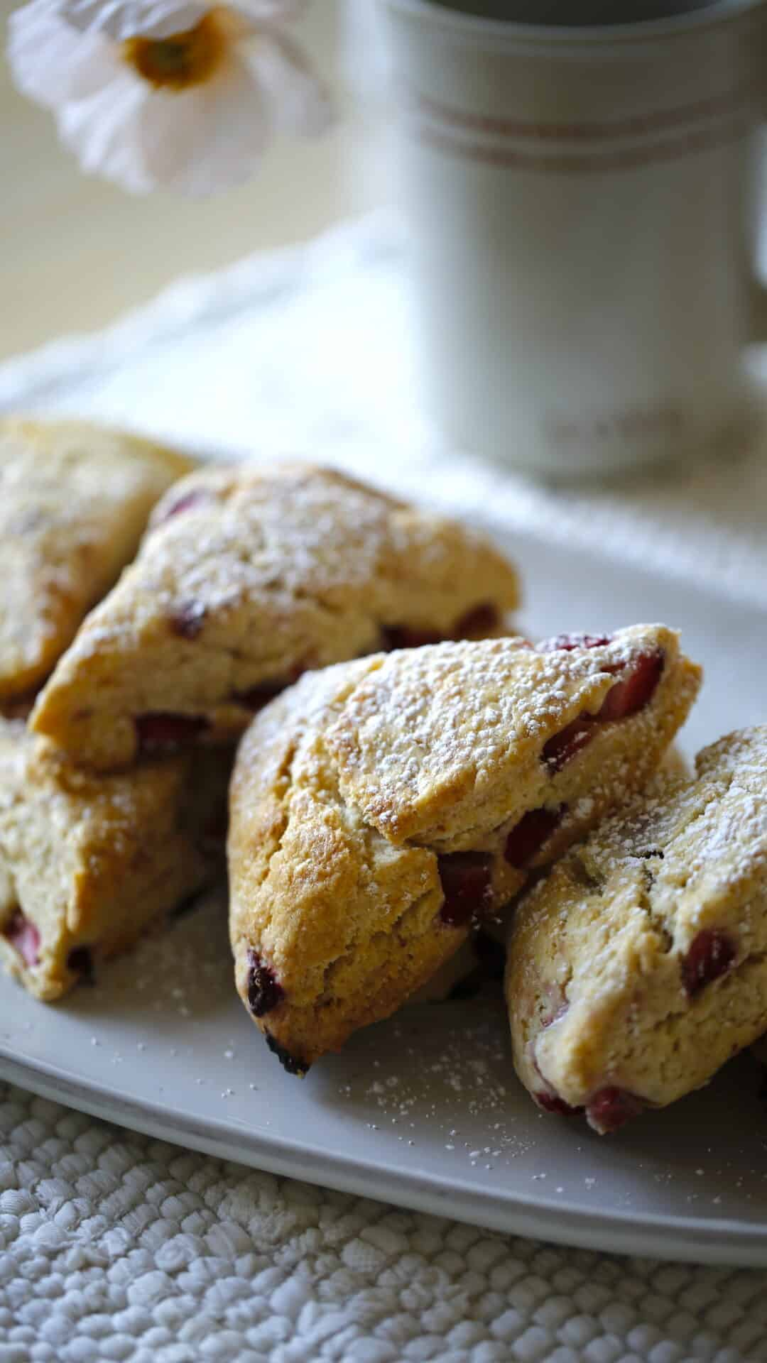Strawberry Scones on a platter with a coffee mug in the background