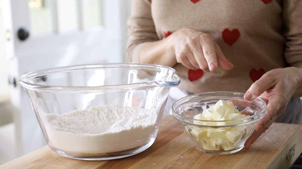 a person adding chilled butter to dry ingredients