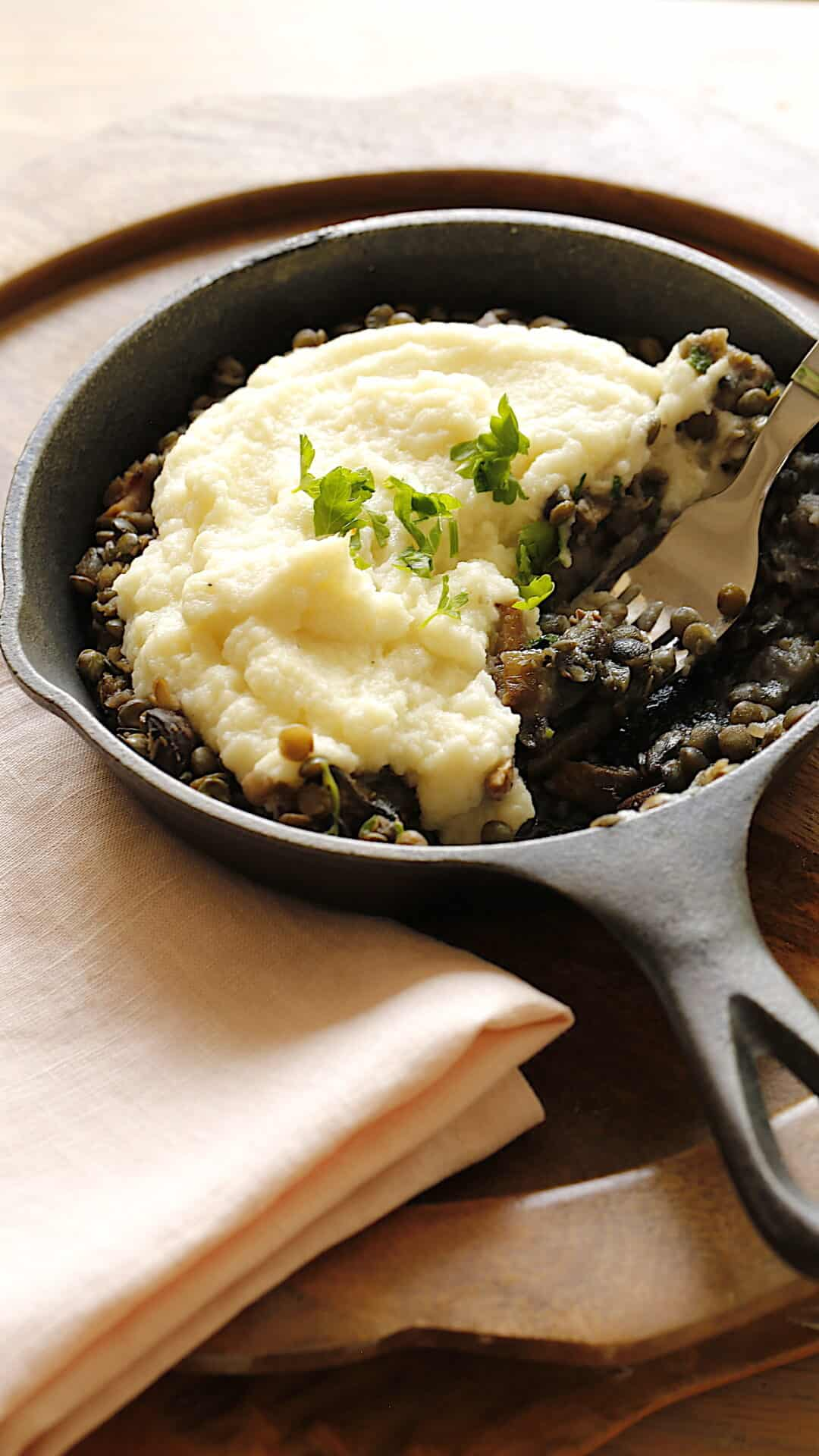a skillet filled with mushrooms and lentil mixture topped with cauliflower mash