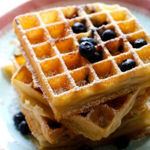 Blueberry Waffles stacked on a plate with fresh blueberries and powdered sugar