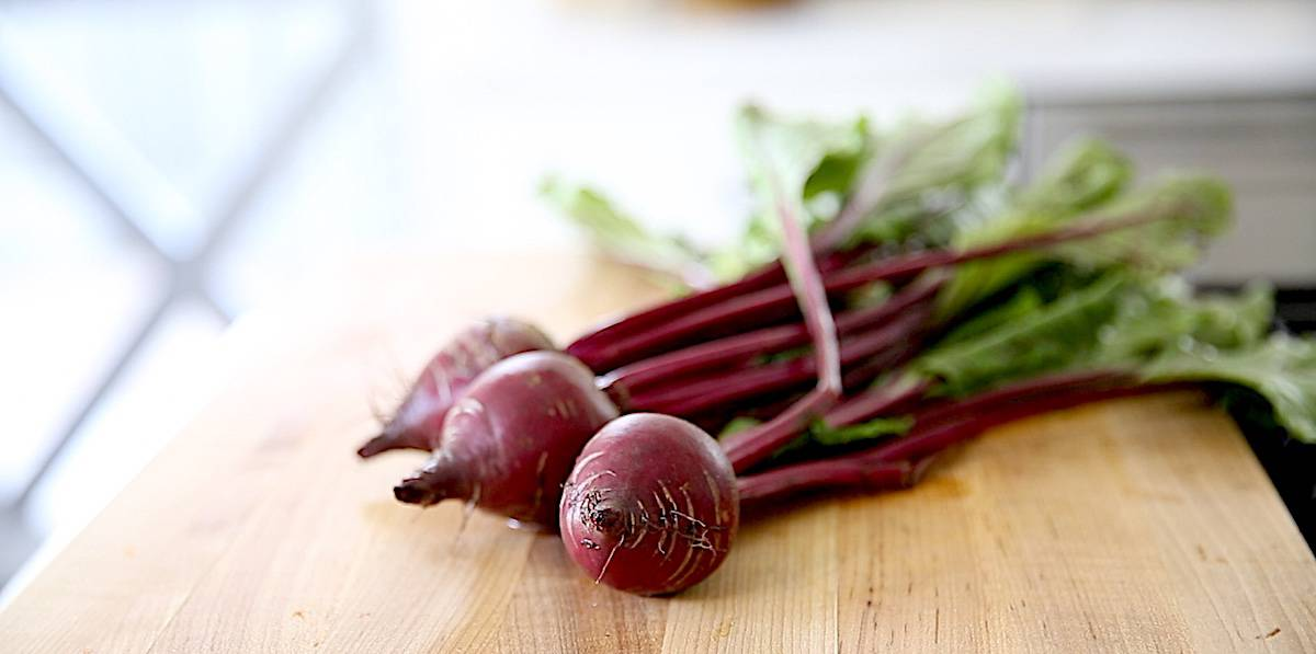 Fresh beets with their greens attached on a cutting board