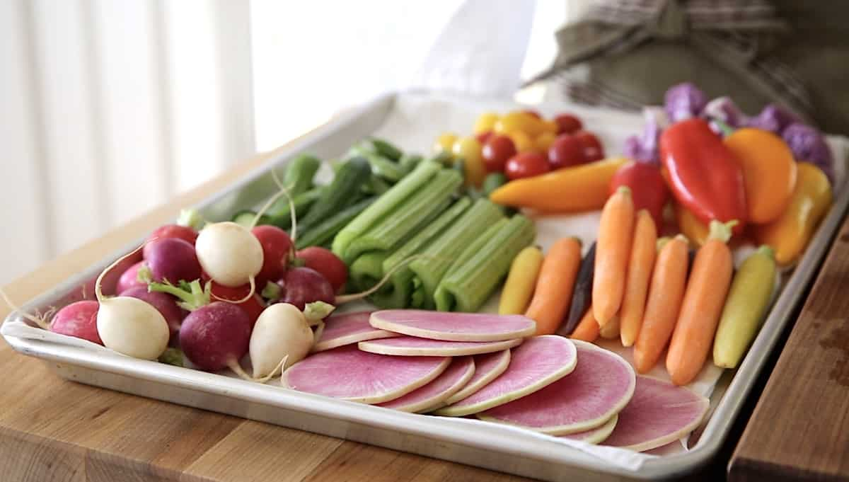 A sheet tray lined with a damp kitchen towel loaded up with colorful vegetables