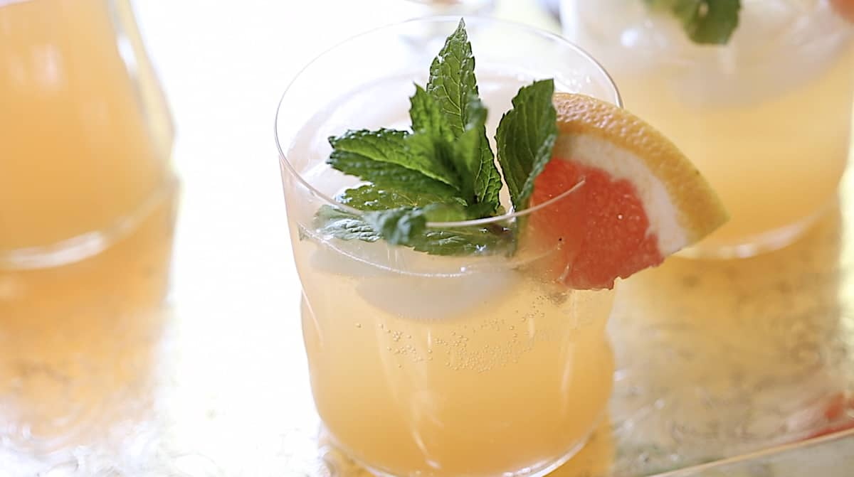 a small glass filled with grapefruit syrup and sparkling water garnished with mint and grapefruit