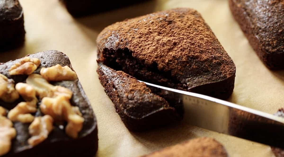 a person slicing a fudgy brownie down the diagnol