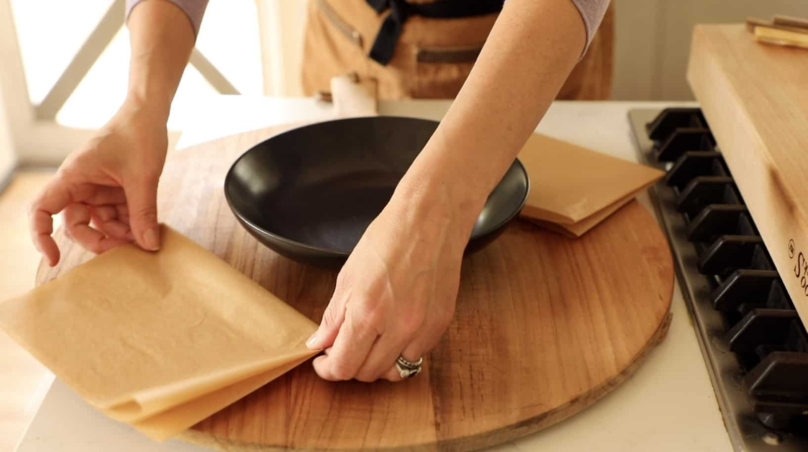 A person placing parchment paper sheets on a board