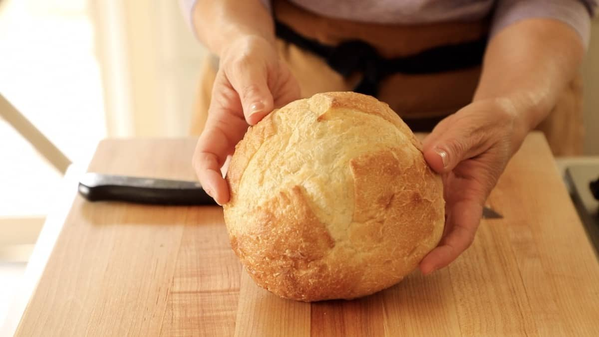 a person holding up a round loaf of bread