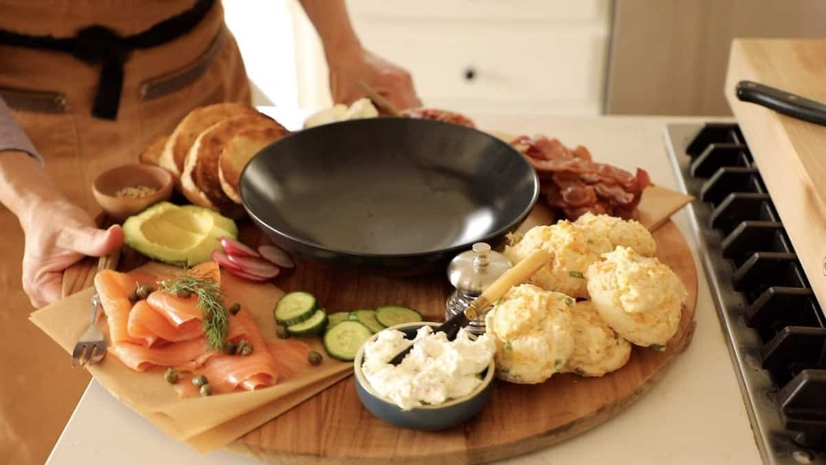 a person taking a board away that is loaded with breakfast foods