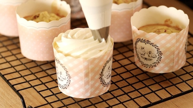 A tight shot of a pastry bag decorating a cupcake with frosting